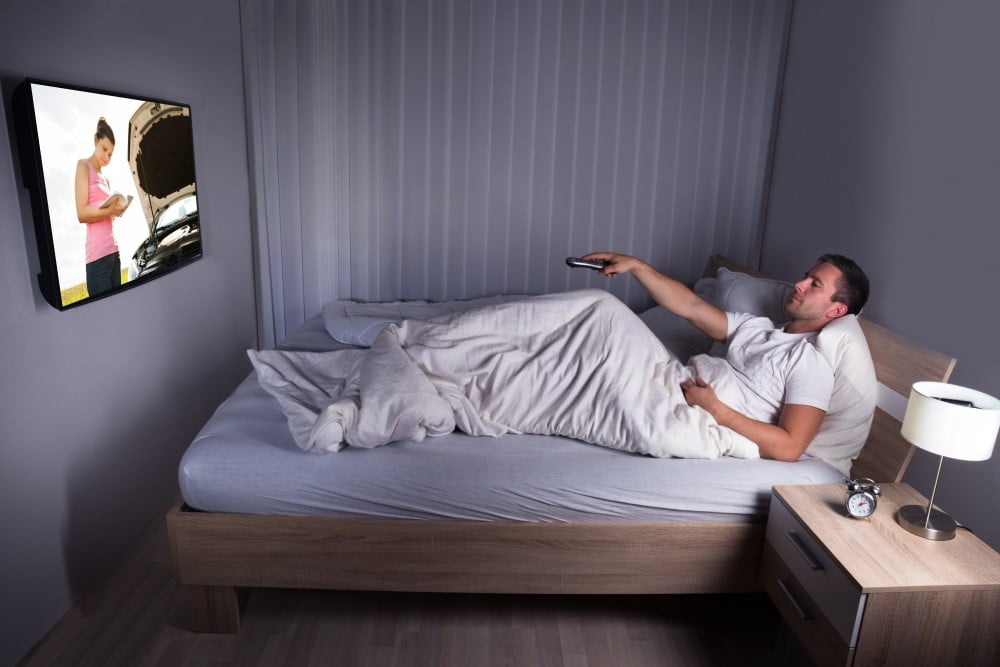 Mand der ser TV i sengen